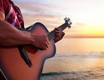 A man plays music on the beach