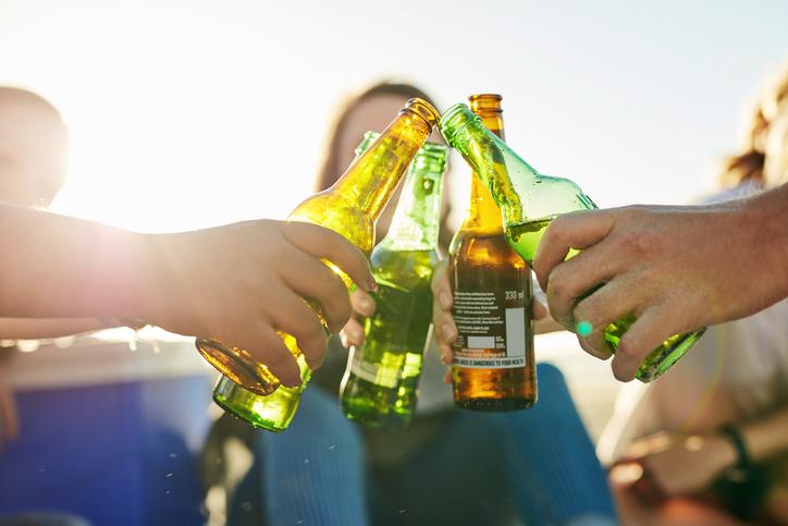 Friends cheers beer bottles