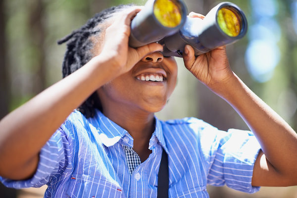 young boy birdwatching with binoculars